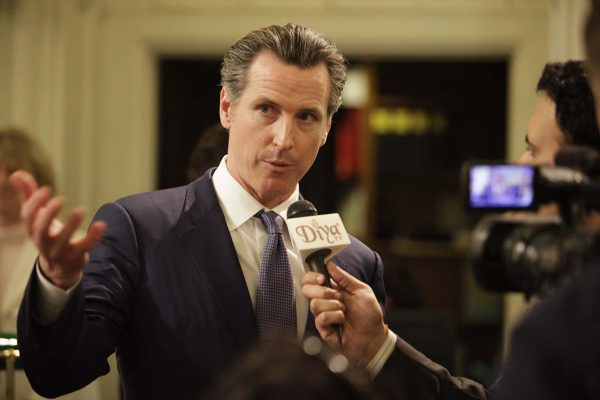 Gavin Newsom speaks into a microphone held by a reporter.