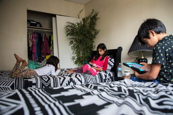 Shukula, Sameera and Mirwais Jan (left to right) in the bedroom they share. Photo by Robbie Short for CALmatters.