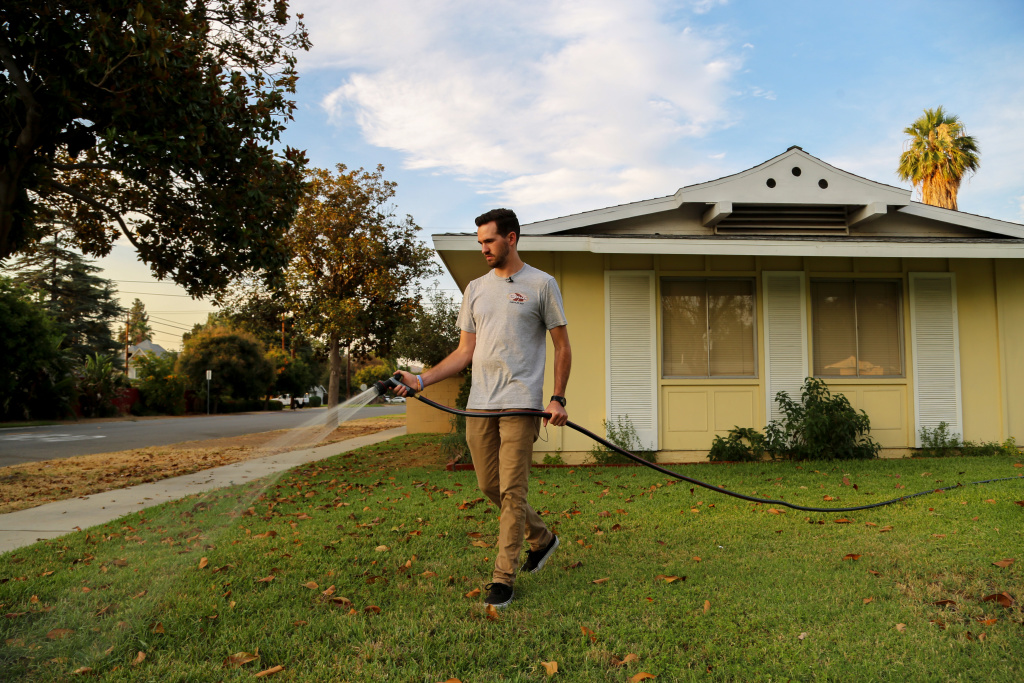 Brandon Miller waters the lawn in front of his Riverside home. Photo by Signe Larsen.