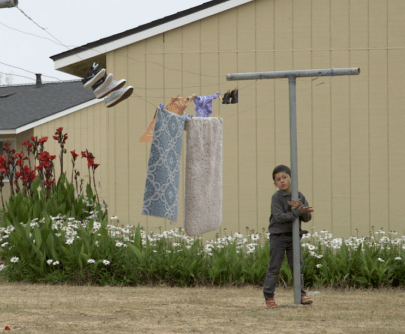 A boy stands next to a clothes line in Watsonville, California, where migrant farmworkers live working the fields. Photo by Byrhonda Lyons for CALmatters