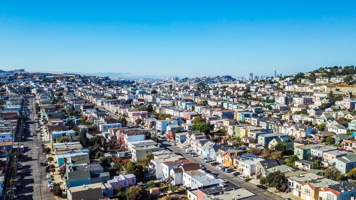 Colorful residential row houses of San Francisco with a view of downtown San Francisco skyscrapers in the distance.