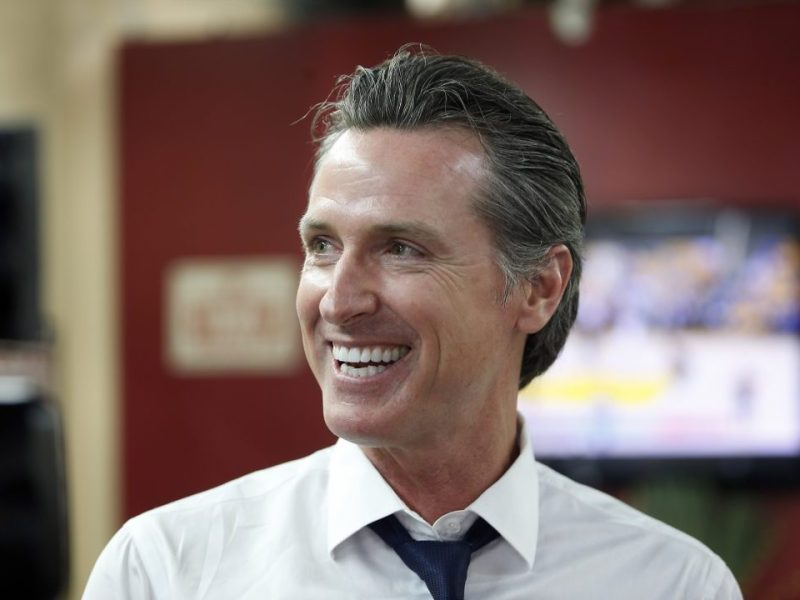 Gavin Newsom smiles at a campaign stop at Stakely's Barber Salon in Los Angeles, as he campaigns for governor. Photo by Damian Dovarganes, Associated Press
