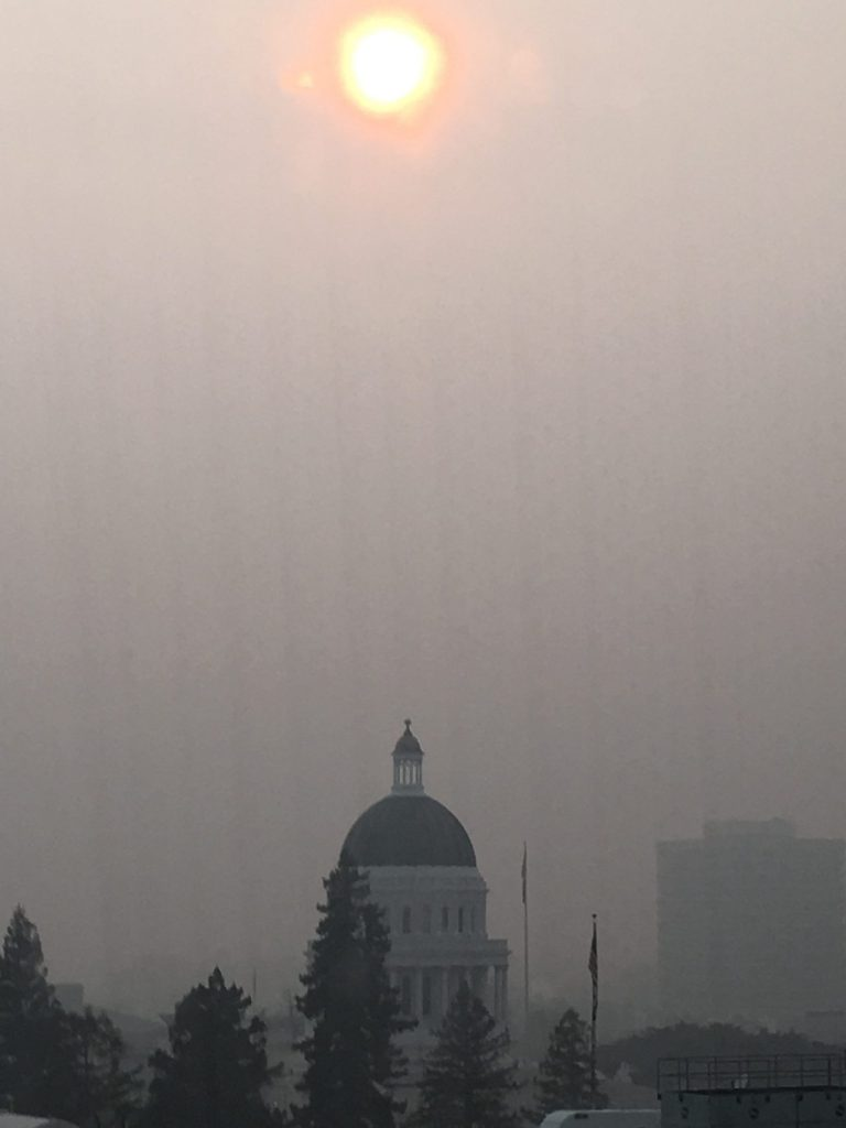 Thick brown fog from the Camp Fire clouds the mid-afternoon sun over the Capitol dome in Sacramento on Thursday, as schools across the state closed due to hazardous air quality. Photo for CALmatters by Shawn Hubler.