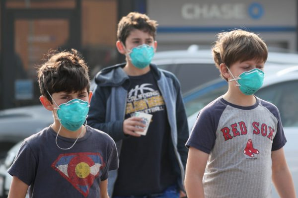OAKLAND, CALIFORNIA - NOVEMBER 16: Ozzie Zinner, left, and his brothers Reuben, 12, and Frank, 10, wear dusk masks as they walk in Montclair Village in Oakland, Calif., on Friday, Nov. 16, 2018. The kids didn't go to school because all schools were closed due to the bad air caused by the fatal Camp Fire that started over a week ago in Paradise, Calif. (Ray Chavez/Bay Area News Group)