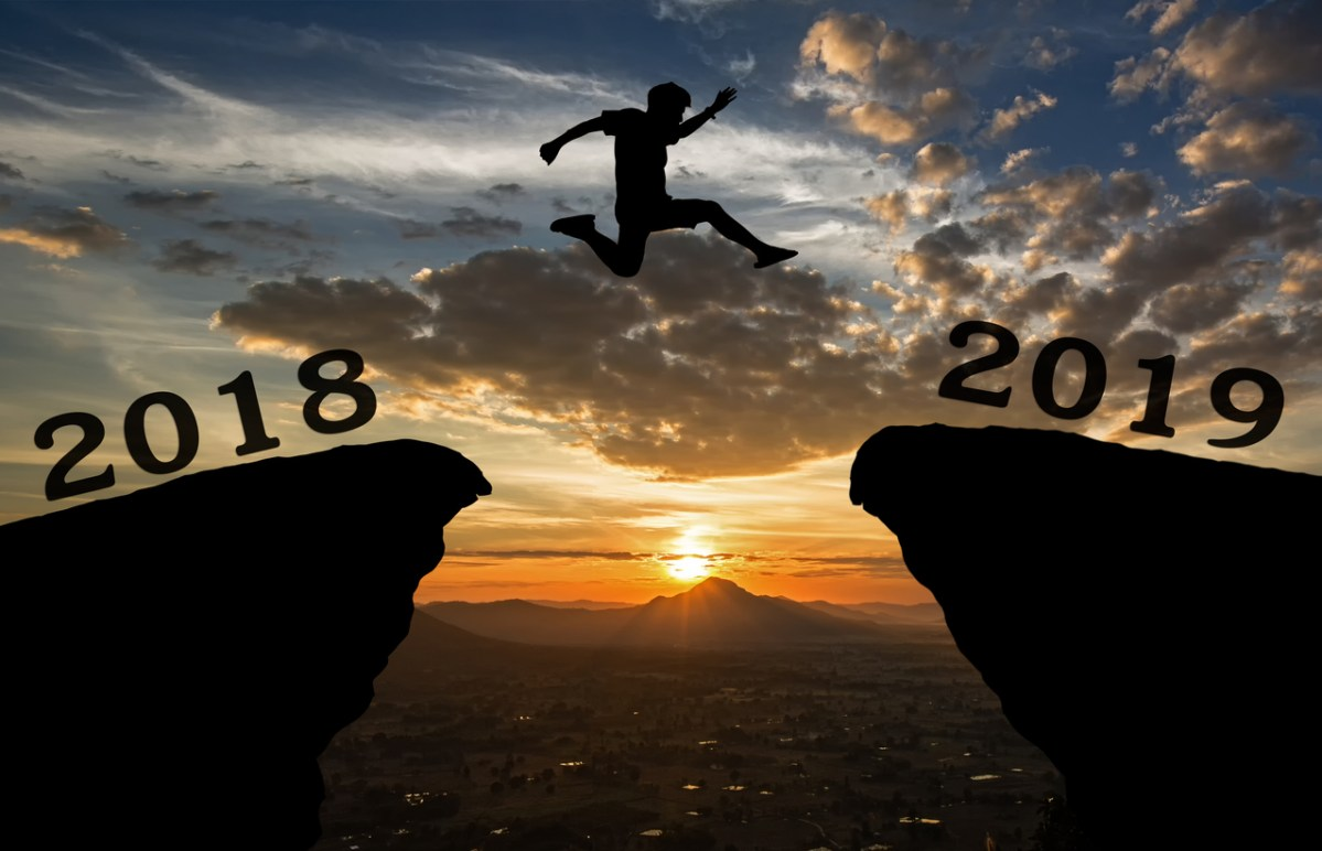A silhouette young man jump between 2018 and 2019 years over the sun and through on the gap of a hill silhouetted against the sky. We look at California's year in politics 2018.