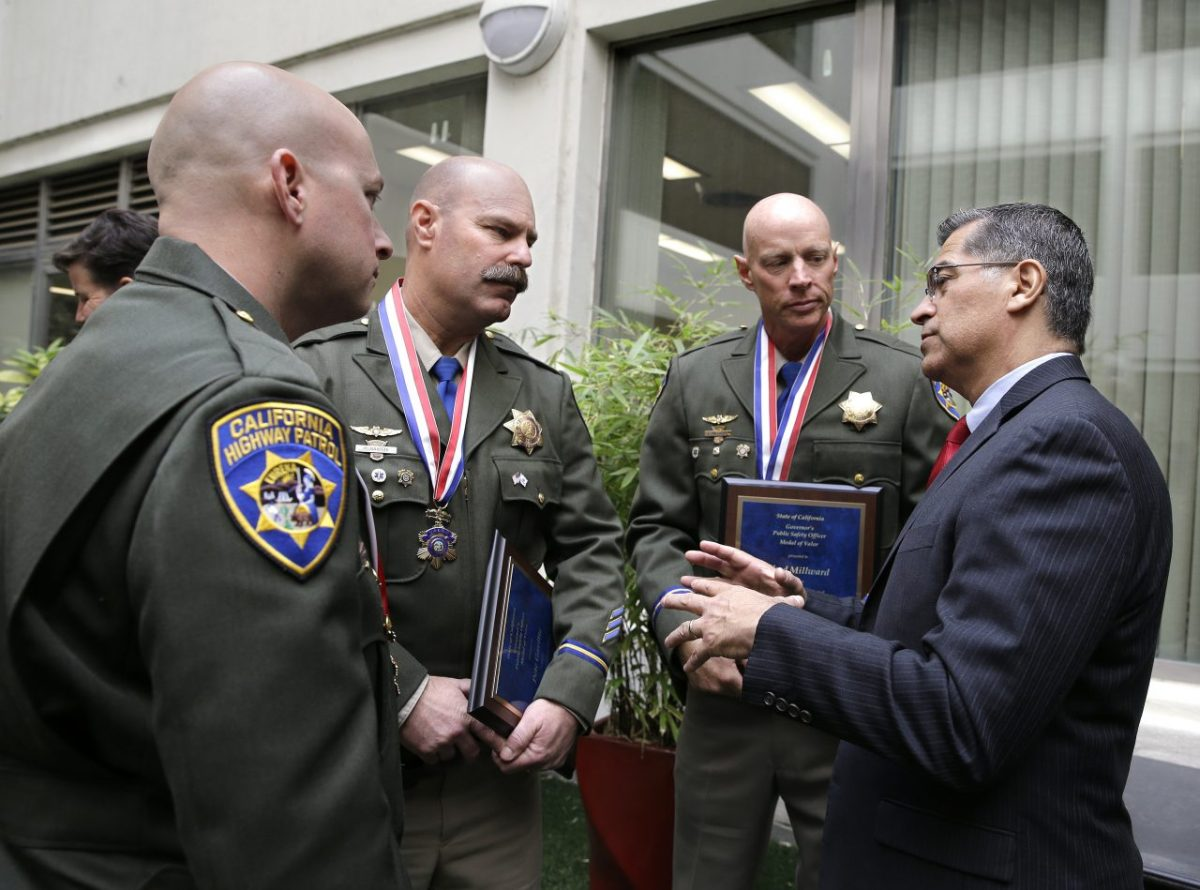 photo of California Attorney General Xavier Becerra, right, talks with California Highway Patrol officers Phil Agdeppa, left, Pete Gavitte, second from left, and Chad Millward, third from left, after they were awarded the public safety officer's Medal of Valor on Oct. 29, 2018 in Sacramento. Photo by Rich Pedroncelli, Associated Press