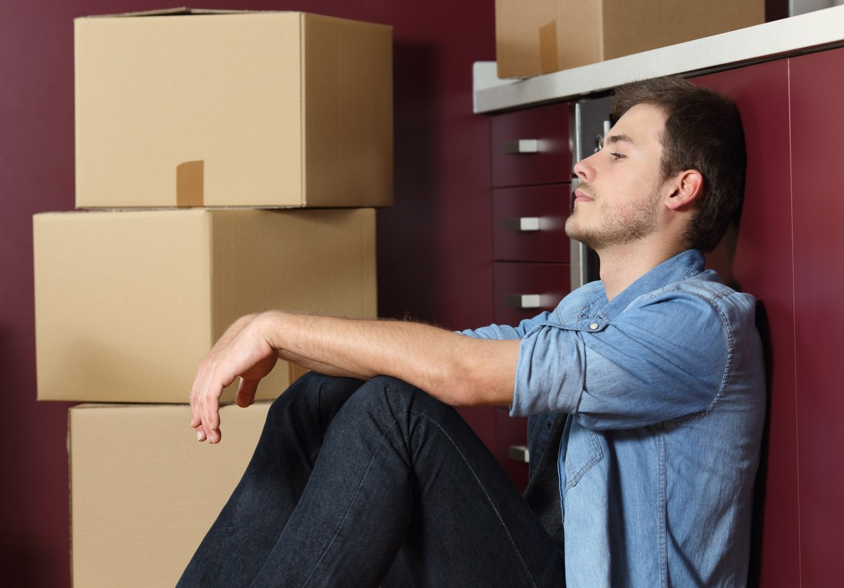 A man sits despondently on a kitchen floor, surrounded by moving boxes.