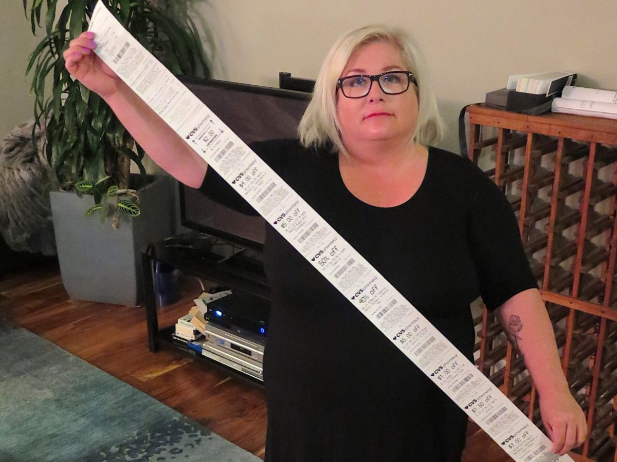 Carol Dahmen poses with a receipt that's more than 4 feet long—for the purchase of a single item. Photo via Kevin Eckery for CALmatters