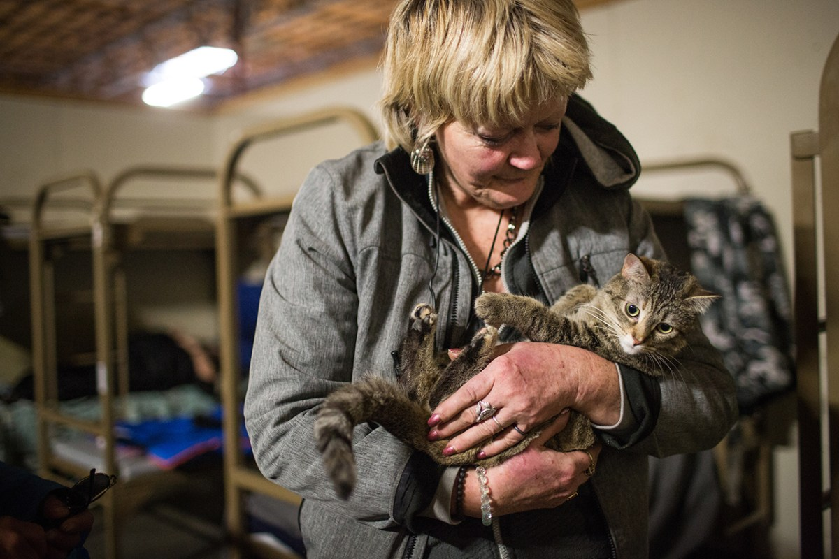 Julie Hemingway cuddles her pet tabby cat, Tammy, at the Sacramento Triage Shelter for people who are homeless in Sacramento. Photo by Max Whittaker for CALmatters.