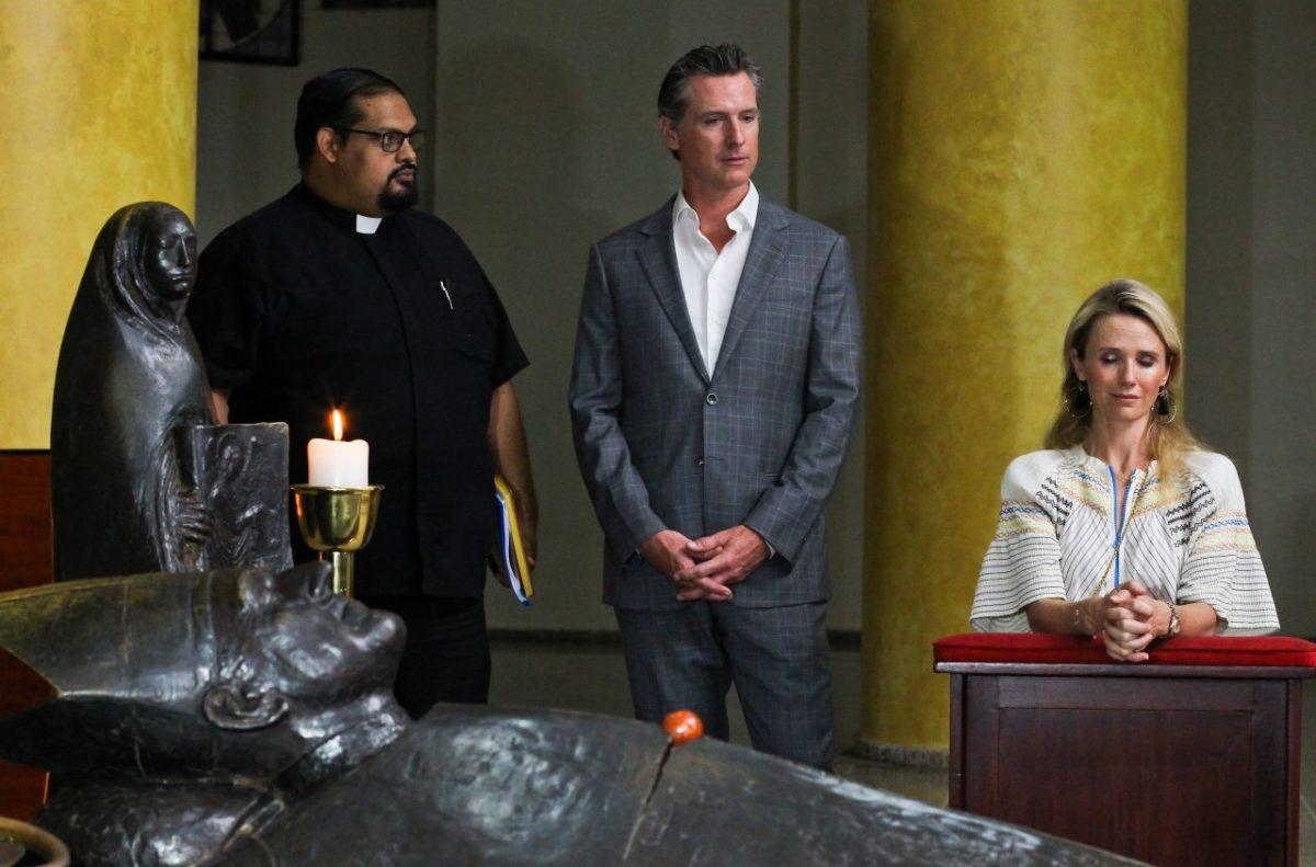 Gov. Gavin Newsom with his wife, Jennifer Siebel Newsom, visit the tomb of Archbishop Oscar Romero at Metropolitan Cathedral in San Salvador, El Salvador, AP Photo/Salvador Melendez, Pool