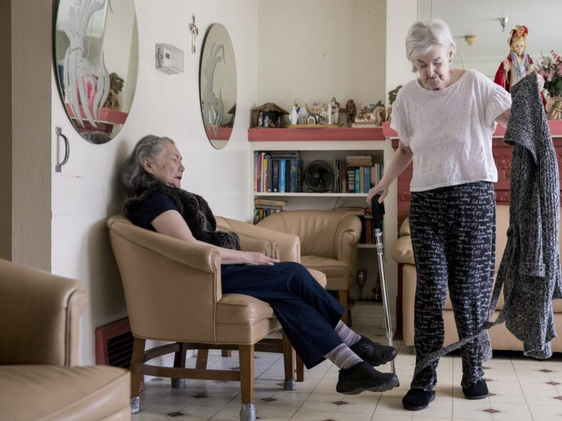 Resident Concepcion Wedell makes her way to the kitchen while walking past Setsuko Letchford in the living room at Palarca's Rest Home in San Francisco. Photos by Jessica Christian, San Francisco Chronicle