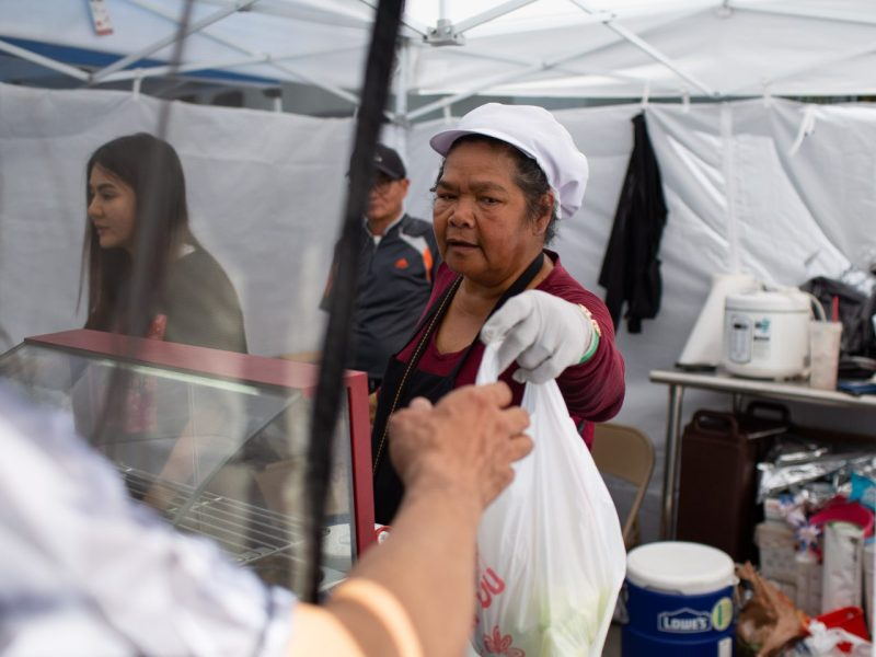 A customer buys Thai food at the East Hollywood Farmers Market, June 6, 2019. Photo by James Bernal for KPCC