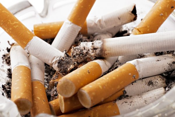 photo of an ashtray filled with cigarette butts.