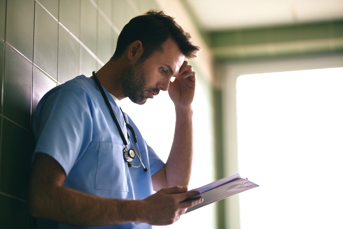 A concerned doctor reads medical information in a hospital hallway. More than 1300 doctors applied for a new California program in which the state pays down their student loans in exchange for their agreement to treat Medi-Cal patients.