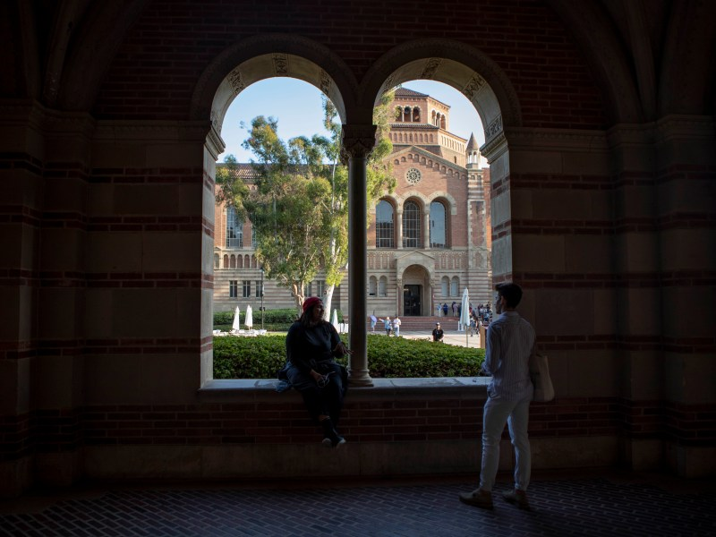 Students sit outside of Royce Hall at UCLA — among the University of California campuses that could experience tuition hikes every year under a pending proposal. File photo by Anne Wernikoff for CalMatters