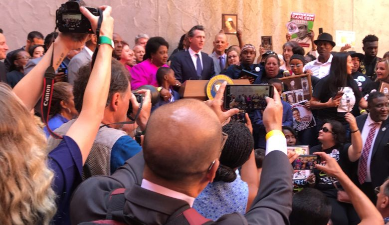 Gov. Gavin Newsom and crowd at signing ceremony for police use-of-force legislation. Photo by Dan Morain, CalMatters