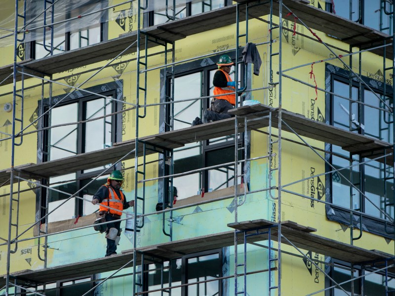 Workers paint a wall on a Factory OS construction project in West Oakland. Photo by Anne Wernikoff for CalMatters