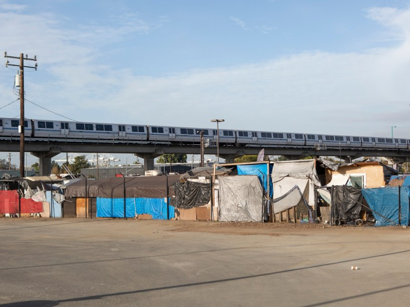 A BART train rides above a homeless encampment in West Oakland. Photo by Anne Wernikoff for CalMatters