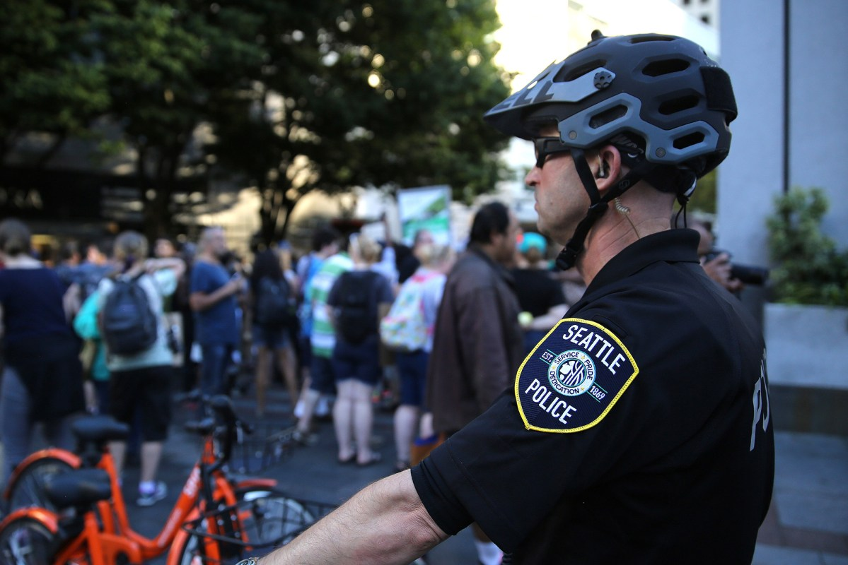A Seattle police officer watches as protesters take part in a Black Lives Matter march, Saturday, August 26, 2017, in Seattle, Washington. Several thousand people attended a downtown rally and then marched through the city to call attention to minority rights and police brutality