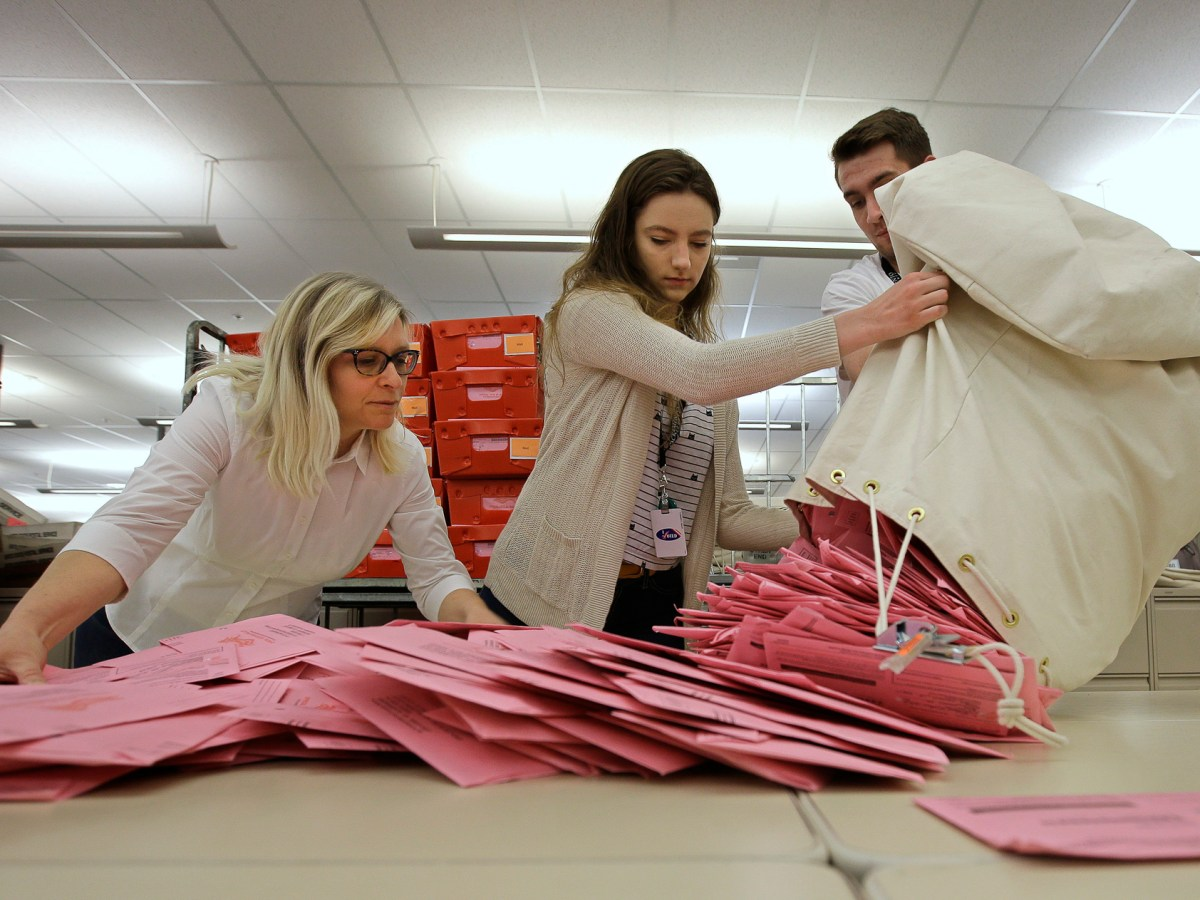 In this June 5, 2018, file photo, election workers Heidi McGettigan, left, Margaret Wohlford, center, and David Jensen, unload a bag of ballots brought in a from a polling precinct to the Sacramento County Registrar of Voters office in Sacramento, Calif. Photo by Rich Pedroncelli, AP Photo