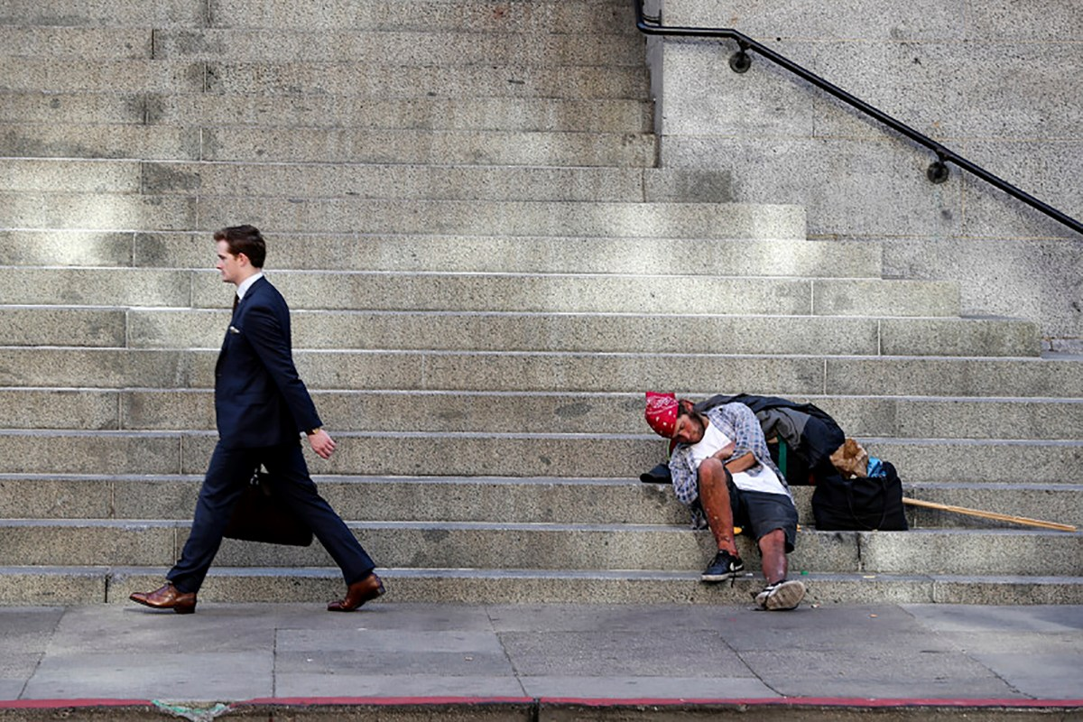 A pedestrian walks past a homeless sleeping on Fifth Street in San Francisco, Calif., on Thursday, Nov. 1, 2018. Photo by Ray Chavez/Bay Area News Group