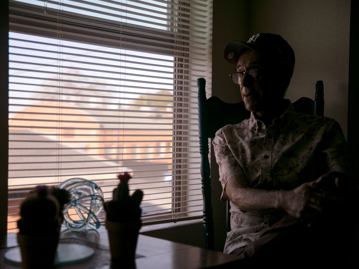 Eduardo Mendoza, a 66-year-old AIDS survivor, sits for a portrait by his apartment window where he can watch the comings and goings of trains and boats in Martinez, California. Photo by Anne Wernikoff for CalMatters