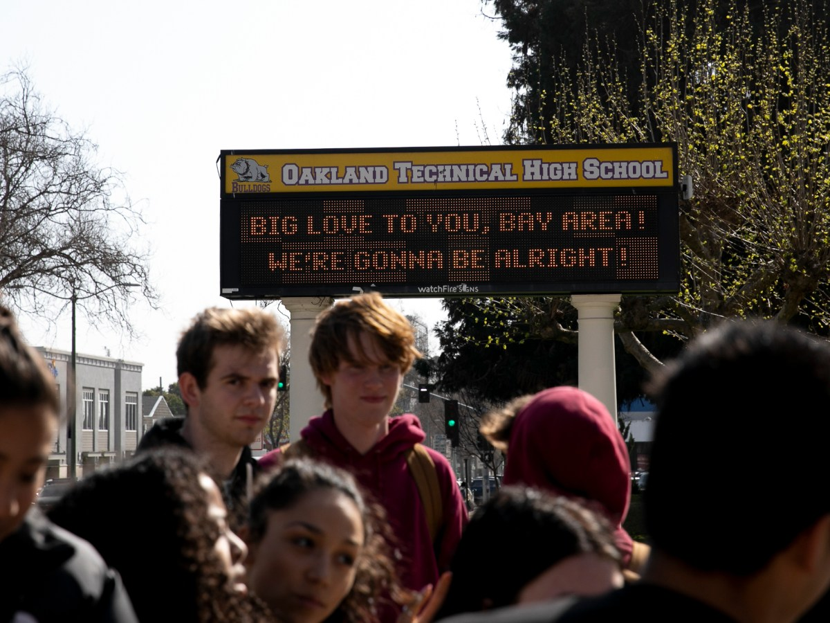 Oakland Technical High School students stand in front of the marquee after it was announced that all Oakland schools would close for three weeks over coronavirus concerns on March 13, 2020. Photo by Anne Wernikoff for CalMatters