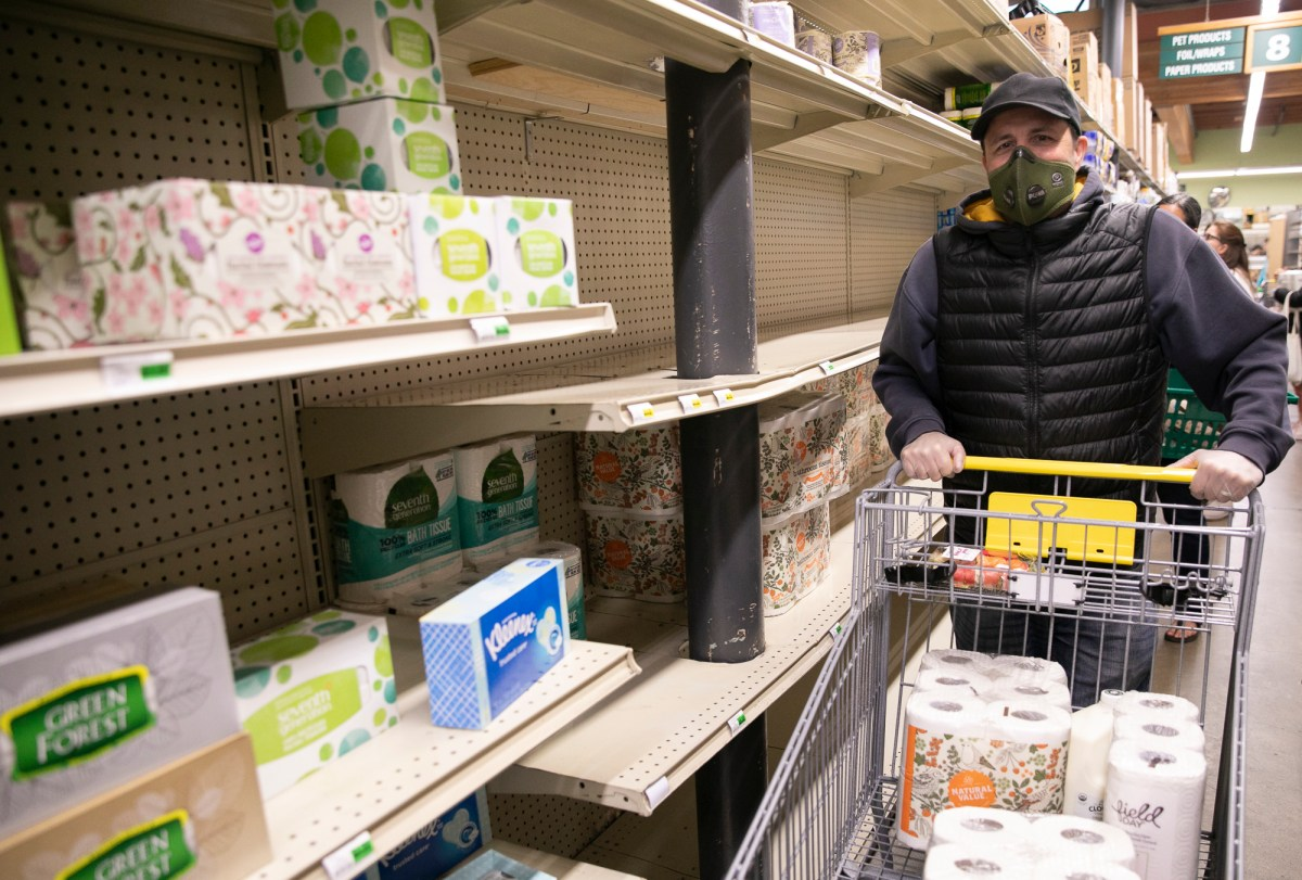 Oakland resident Stefan Gustafsson wears a protective mask and gloves as he shops for necessities at Berkeley Bowl on March 13, 2020.