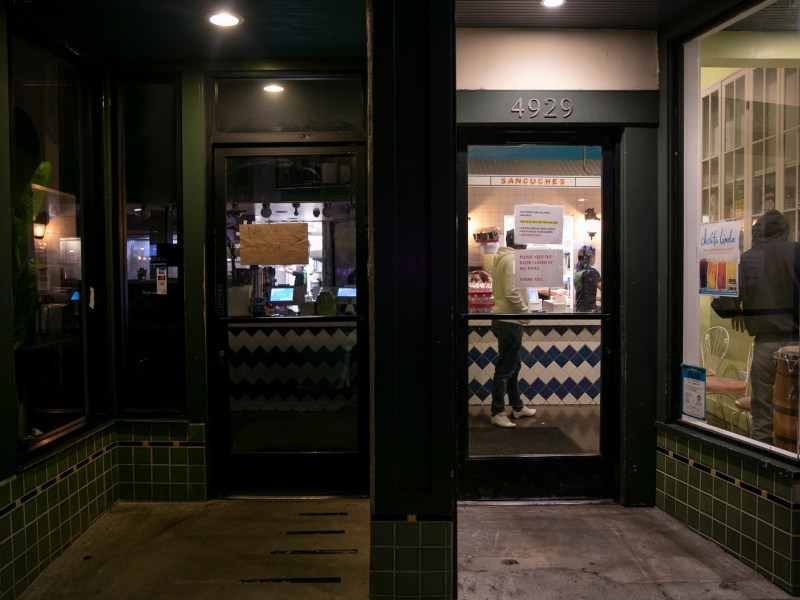 A sign hangs from the door at Cholita Linda, an Oakland counter-service restaurant, informing customers to go next door for take out following an order for Alameda and surrounding counties to shelter in place until April 7 in an effort to curb the spread of the novel coronavirus