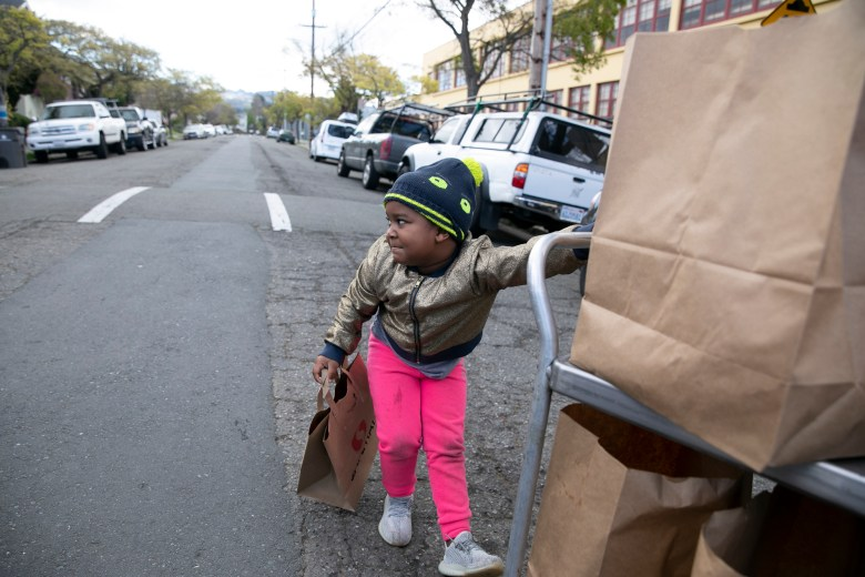 Hannah Jones, 5, pulls a cart full of free meals to her family car at Sankofa Academy. Children and their families from anywhere in the district can pick up multiple days worth of lunches and breakfasts from a dozen sites across the city during the mandated school closure. Photo by Anne Wernikoff for CalMatters