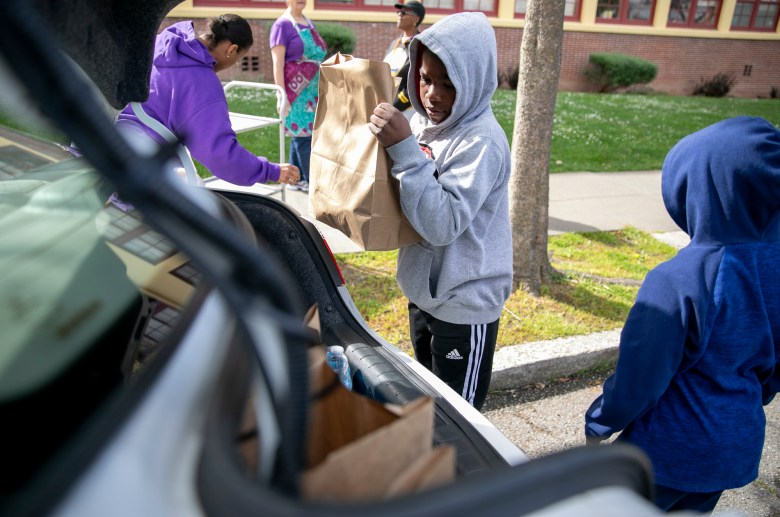Kaden Minor, 10, helps to load the family car with bagged meals at Sankofa Academy in Oakland. Children and their families from anywhere in the district can pick up multiple days worth of lunches and breakfasts from a dozen sites across the city during the mandated school closure. Photo by Anne Wernikoff for CalMatters
