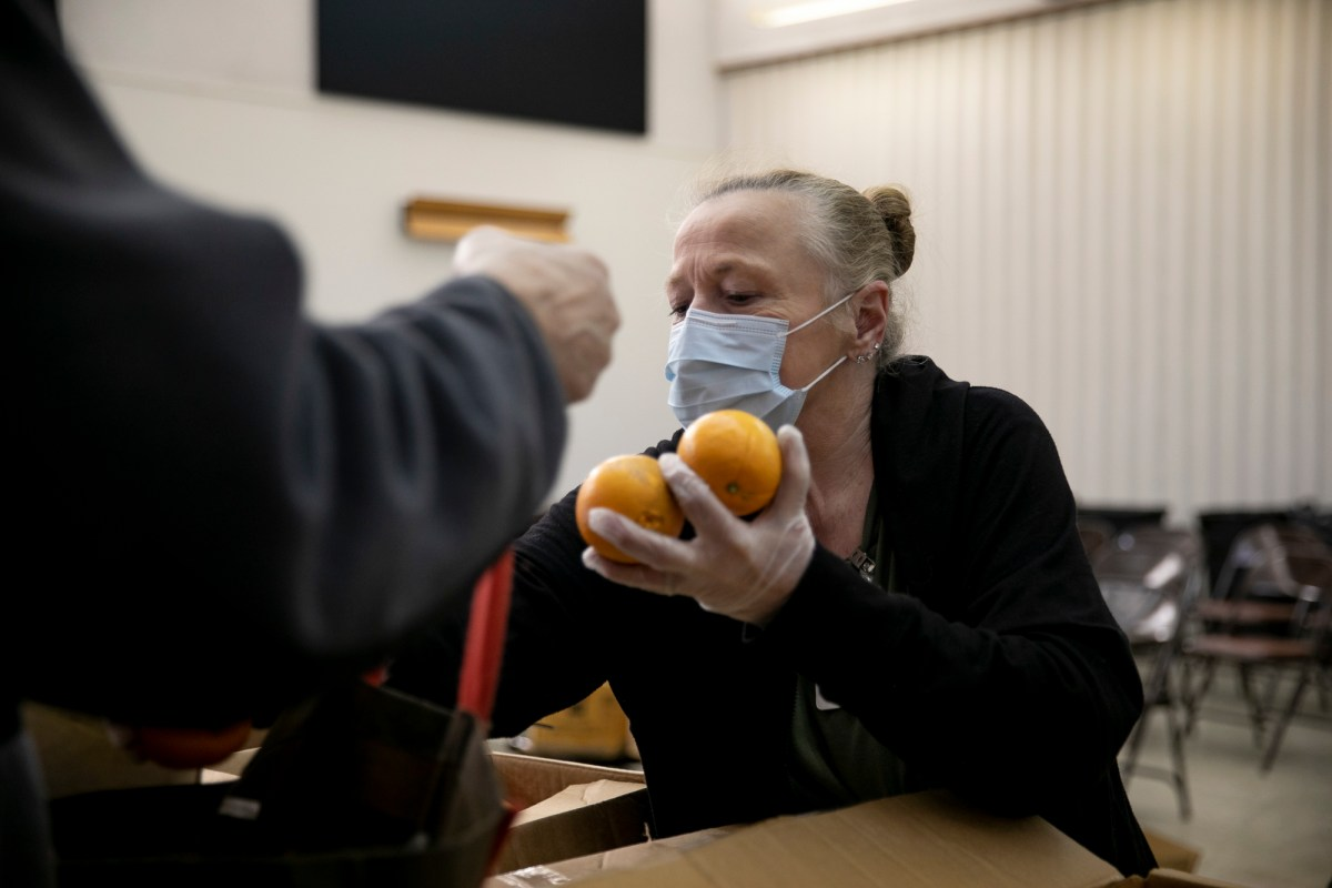 Food bank volunteer Betty Kimmel wears a protective mask as she hands out oranges to seniors at Teamsters 315 Hall in Martinez on March 19, 2020. Photo by Anne Wernikoff for CalMatters