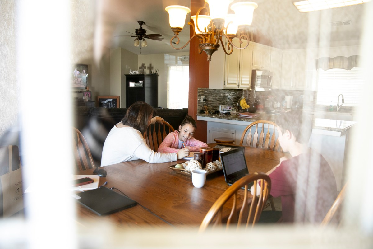 Lucia Soares helps her two younger children, Emily, 9, and Daniel, 16, with their school work in their Modesto home. Photo by Anne Wernikoff for CalMatters