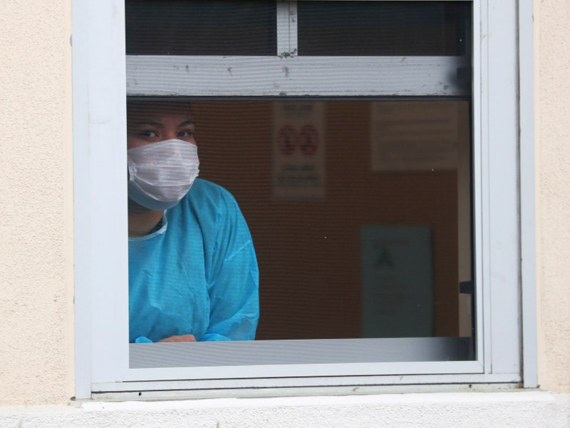 A worker at the Firehouse Clinic looks out a window at a testing site for the COVID-19 virus along Huntwood Avenue near Fire Station 7 in Hayward. The state is now allowing all uninsured Californians to be tested and treated for COVID-19 at community clinics and health centers, regardless of immigration status. Photo by Aric Crabb/Bay Area News Group