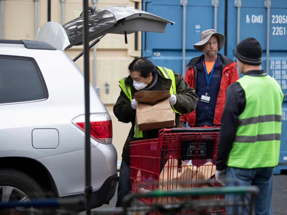 Martin Lee, a local resident, loads a bag of food into a vehicle at the Sunnyvale Community Services food distribution site, Wednesday, March 18, 2020, in Sunnyvale, Calif. The social services organization has seen a bid drop in their volunteers, many of whom are senior citizens. Photo by Karl Mondon/Bay Area News Group