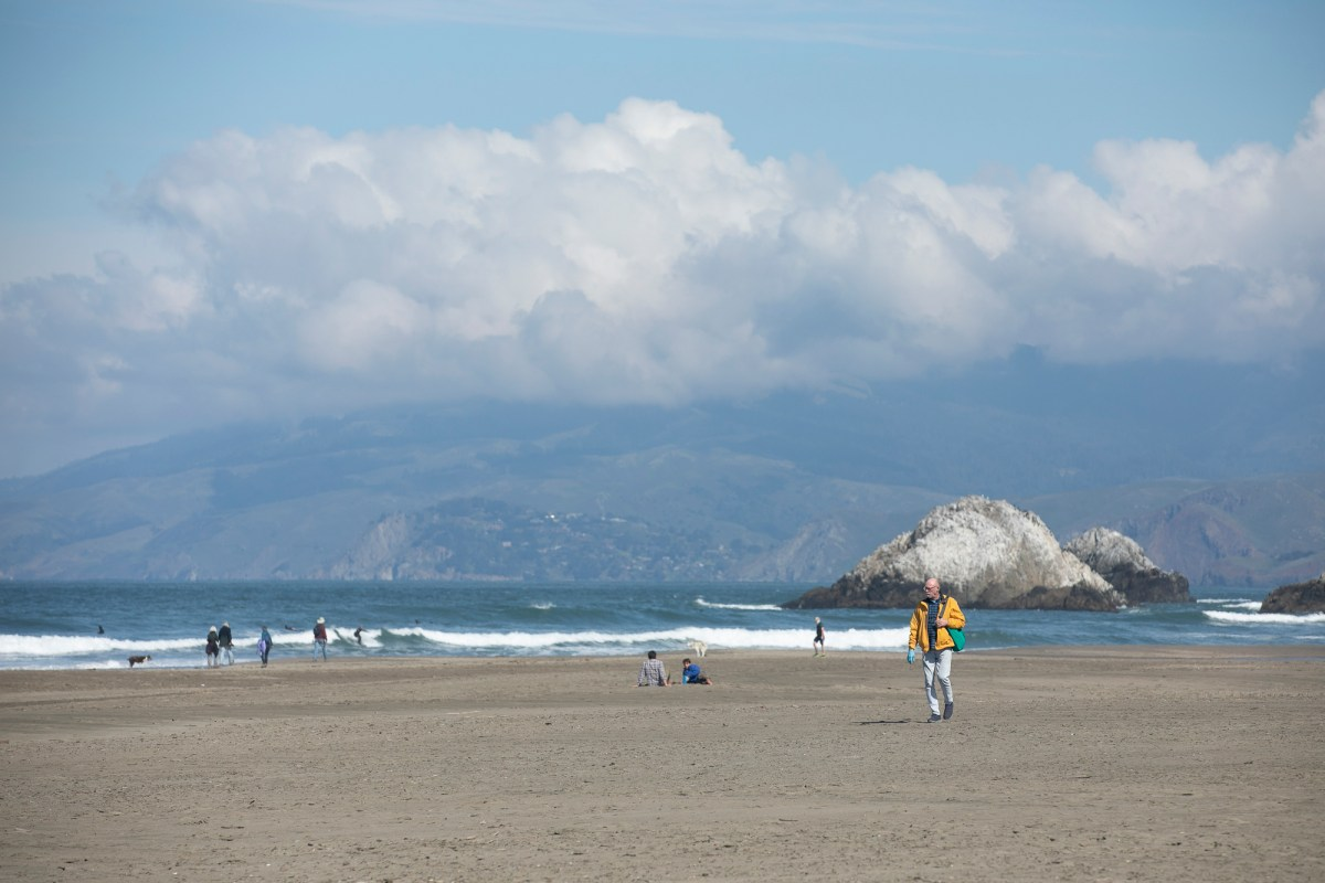 A small crowd of beach goers at Ocean Beach in San Francisco on April 7, 2020. California is entering the fourth week of sheltering in place to limit the spread of the novel coronavirus. Photo by Anne Wernikoff for CalMatters