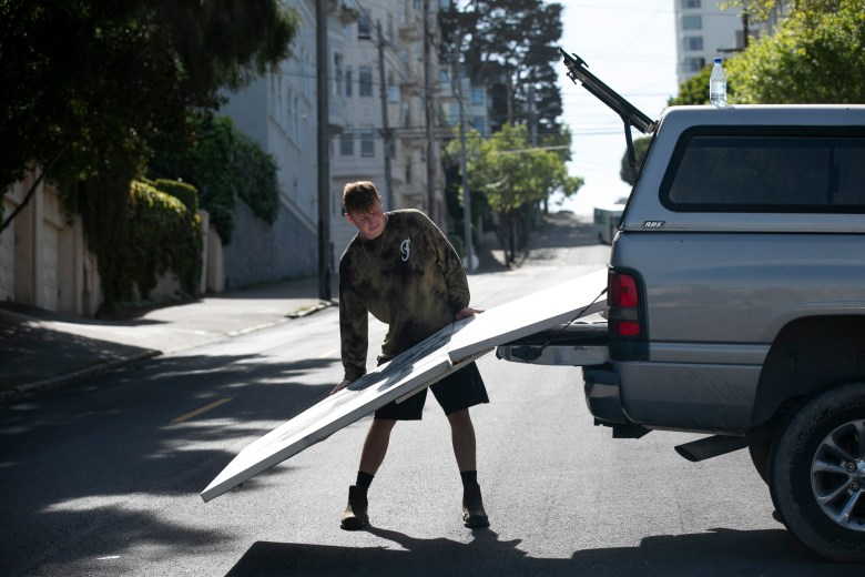 Painting major Niko Schumann picks up a canvas from the closed Chestnut Street campus of San Francisco Art Institute, where he is a junior. Schumann says he will likely transfer to California College of the Arts next year to finish his degree. Photo by Anne Wernikoff for CalMatters