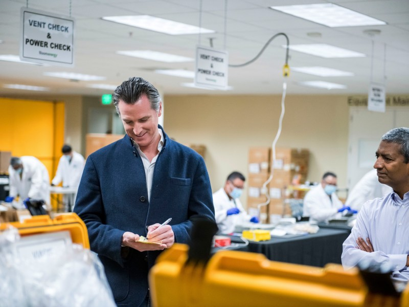 Gov. Gavin Newsom writes down a note during a March 28 tour of the Bloom Energy in Sunnyvale, which refurbished ventilators to meet the COVID-19 pandemic. This week Newsom announced the state would loan 500 ventilators to the national stockpile for use by New York and other states, and that it would share excess masks from its massive purchase of them. Photo by Beth LaBerge/Pool Photo via AP
