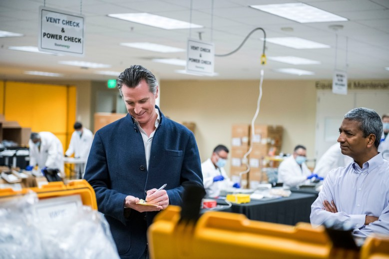 In this March 28, 2020, file photo, Gov. Gavin Newsom writes down a note during a tour of the Bloom Energy in Sunnyvale. The company has switched over to refurbishing ventilators as an increasing number of patients experience respiratory issues as a result of COVID-19. Gov. Newsom announced Monday, April 6, 2020, the state would loan 500 ventilators to the national stockpile for use by New York and other states experiencing a crush of coronavirus-related hospitalizations. Photo by Beth LaBerge/Pool Photo via AP