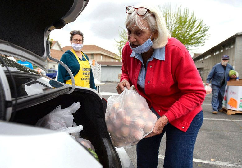 Volunteer Cheryl Phelps, right, helps load food at a food bank giveaway held at Easton Presbyterian Church Monday, April 6, 2020 in Easton. Photo by Eric Paul Zamora, The Fresno Bee