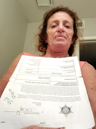 Lori Waldman holds up her eviction notice from the Riverside sheriff's department. She and her 87-year-old father were scheduled for a lock-out eviction this week but until now have been able to stay in their apartment. Photo courtesy of Lori Waldman