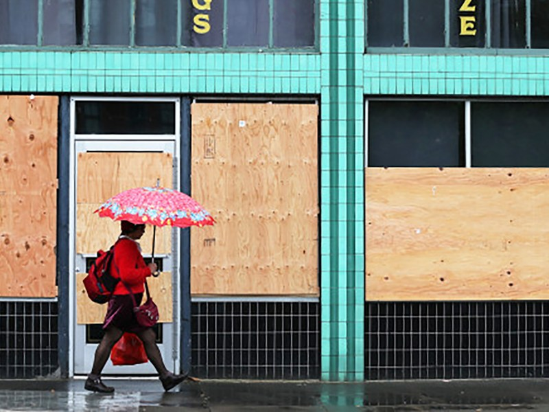 A pedestrian walks past boarded up windows of a business in Oakland on the the eighth day of the shelter-in-place order on March 24, 2020.One month into the order, California's economy has entered a recession. Photo by Ray Chavez, Bay Area News Group