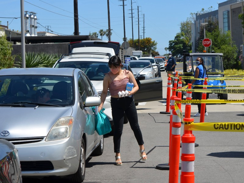 A student walks back to her car after picking up eggs, milk, produce and dried goods from the weekly drive-thru food pantry at Santa Monica College. Photo by Mikhail Zinshteyn for CalMatters