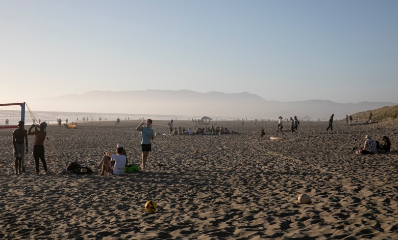 Beach-goers enjoy the sunset at Ocean Beach on Memorial Day in San Francisco on May 25, 2020. Photo by Anne Wernikoff for CalMatters
