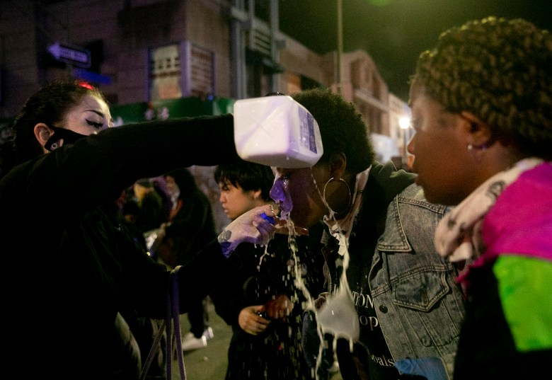 A demonstrator has milk poured over her eyes after the Oakland police used tear gas to disperse protesters during a protest calling for justice for victims of police brutality May 29, 2020 Downtown Oakland. Thousands took to the streets Friday night in solidarity with protesters in Minneapolis against the killing of George Floyd by Minneapolis police earlier this week. Photo by Anne Wernikoff for CalMatters