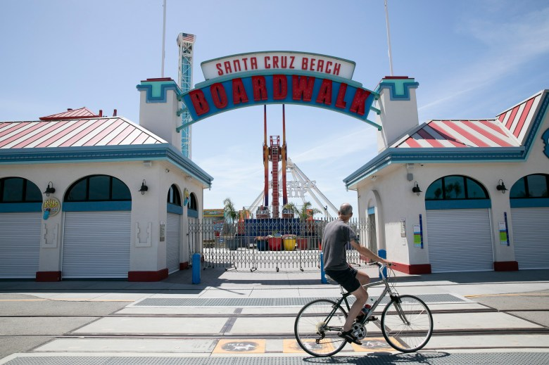 A man bikes past the locked gate at The Santa Cruz Beach boardwalk on May 7, 2020. Photo by Anne Wernikoff for CalMatters