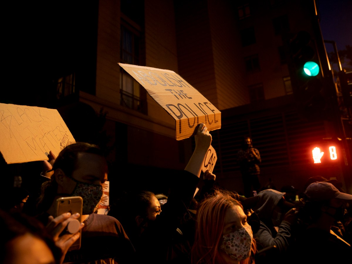 Protesters hold up a signs during a demonstration May 29, 2020 Downtown Oakland. Thousands took to the streets Friday night in solidarity with protesters in Minneapolis against the killing of George Floyd by Minneapolis police earlier this week. Photo by Anne Wernikoff for CalMatters
