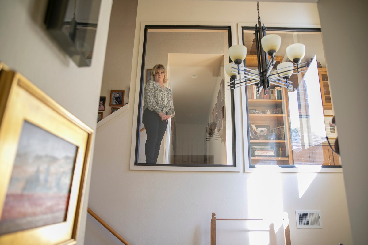 Teresa Pasquini looks into the foyer of her home where her son, who has schizoaffective disorder, once attempted suicide before being discovered by his younger sister. Photo by Anne Wernikoff for CalMatters