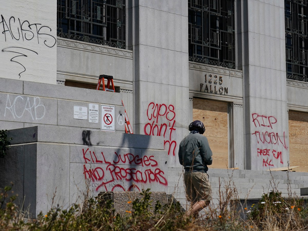"""A man walks past wooden boards and graffiti outside of the Alameda County Courthouse in Oakland on July 26, 2020. Last night, protests in downtown Oakland in support of racial justice and police reform turned violent when """"agitators"""" among the demonstrators set fire to a courthouse, vandalized a police station and shot fireworks at officers, according to authorities. Photo by Jeff Chiu, AP Photo"""
