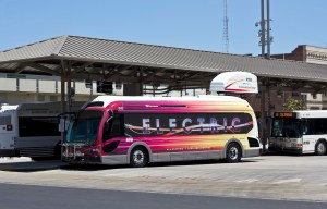 """An all-electric Proterra bus operated by San Joaquin Regional Transit District, shown beside its """"Fast Charging"""" station. Image via Creative Commons. California's clean-air programs take a hit in new funding cuts."""